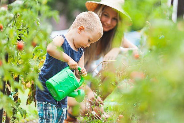 cute-toddler-helphing-mom-in-the-garden-4AV86FN
