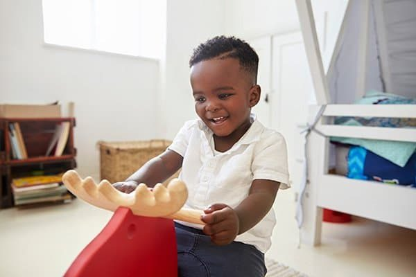 young-boy-sitting-on-ride-on-toy-in-playroom-PLA57QV